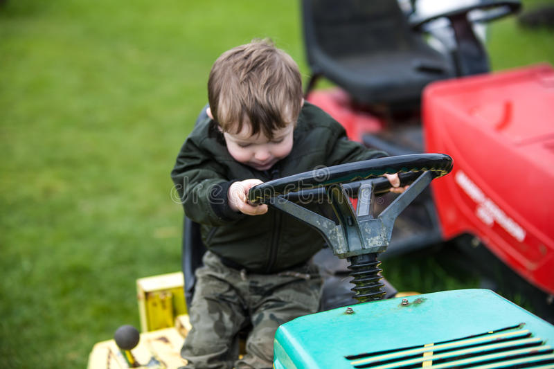 Child on lawn mower stock image