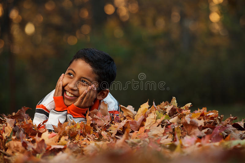 Child Laying on Autumn Leafs stock photos