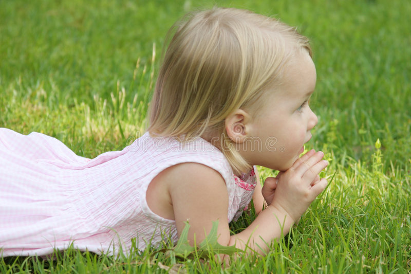 Child laying on grass stock photo
