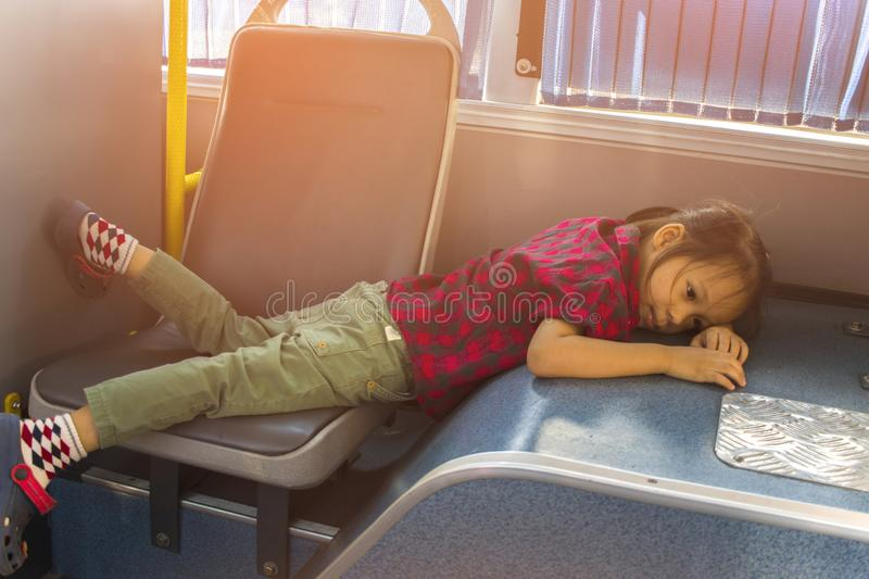 A child lays on the seat in the shaking bus. alone stock image