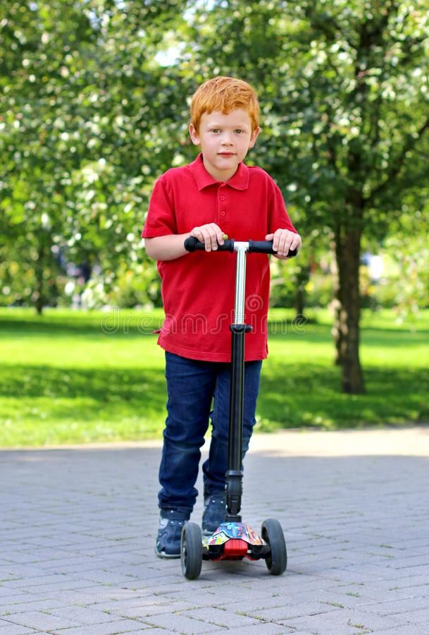 Child learn to ride scooter in a city park on sunny summer day. Cheerful little boy with ginger hair posing with a stock images