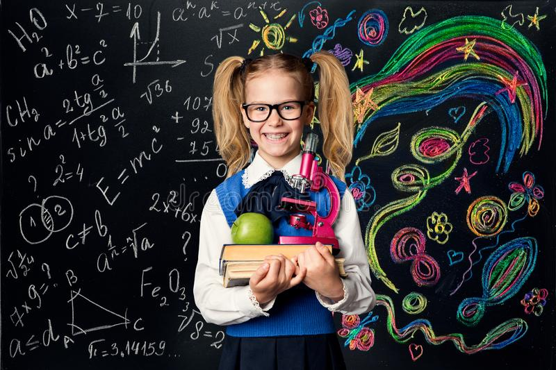 Child Learning Creativity and Mathematics, Creative School Kid Girl Student with Books over Art Blackboard royalty free stock image