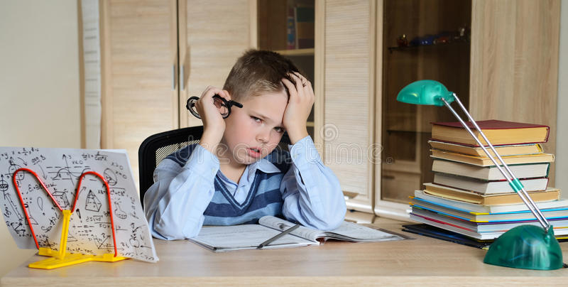 Child with learning difficulties. Tired boy doing homework. Education. stock photo