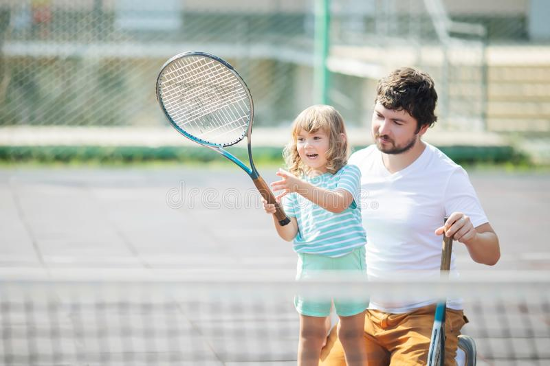 Child learning to play tennis with her father on outdoor court. Little girl with tennis racket. Active exercise for kids and family royalty free stock photography