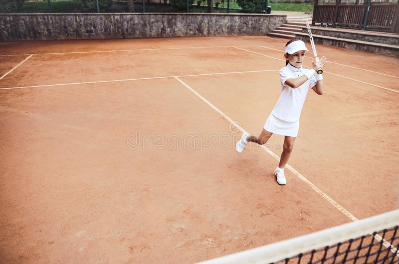 Child learning to play tennis in the sport club. Full length shot of a little girl tennis player on clay court. Sporty child girl. Hits the ball with a racket royalty free stock photos