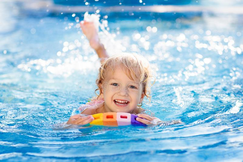 Child learning to swim. Kids in swimming pool stock image