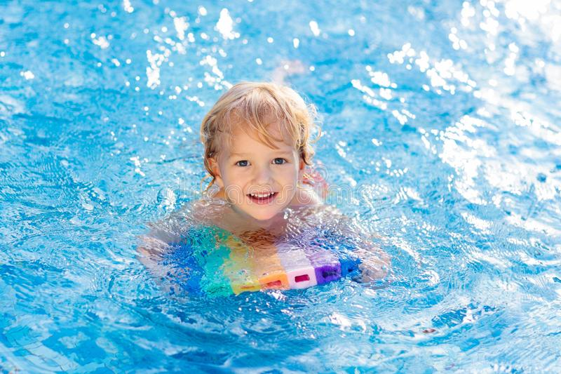 Child learning to swim. Kids in swimming pool stock images