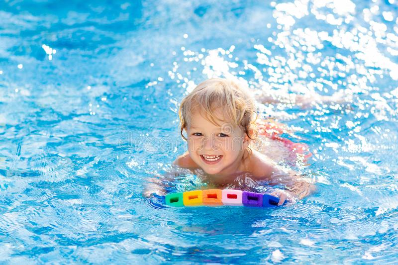Child learning to swim. Kids in swimming pool. Child learning to swim in outdoor pool of tropical resort. Kids learn swimming. Exercise and training for young royalty free stock photos