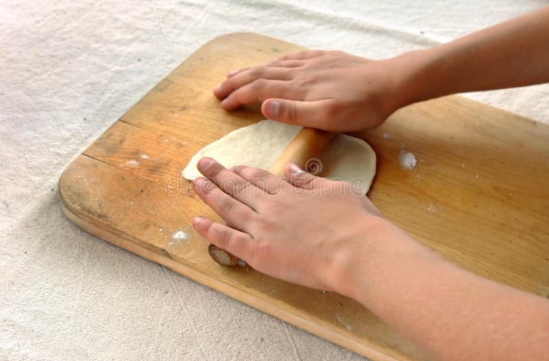 Child Learns Home Made Tortilla Making. Young child learns to roll out the dough to form tortillas. She is using an old cutting board and wooden rolling pin stock photos