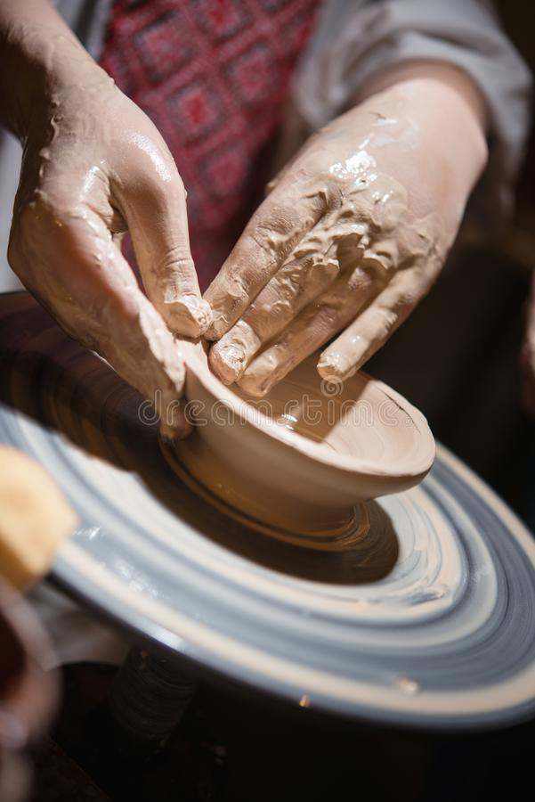 Child learns how to sculpt a ceramic plate. On a potterheel. Close-up of a child`s hand stock photos