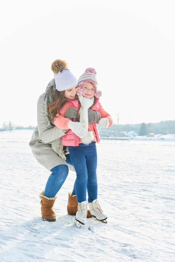 Child learns ice-skate with help. From mother in winter stock images