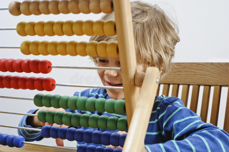 Child learns to count. A young boy learns to count using an abacus stock images