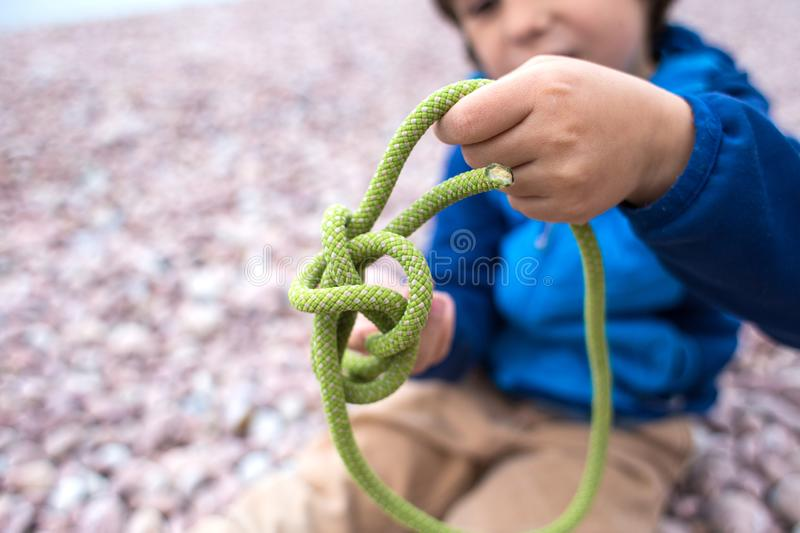 A child learns to knit a knot from a rope stock photo