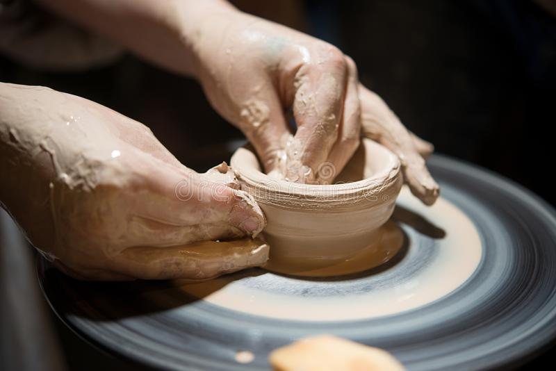 Child learns to make pottery on the potter`s wheel. Child learns to make pottery on a potter`s wheel, close-up royalty free stock image