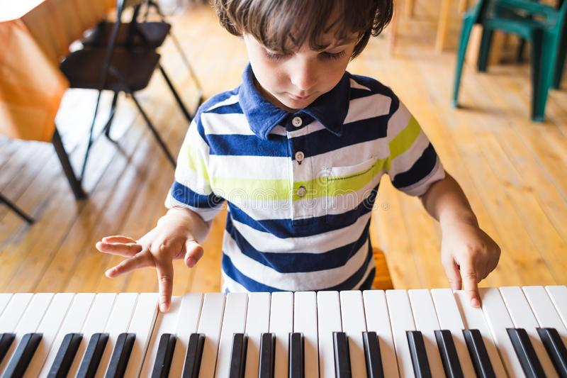 A child learns to play the piano royalty free stock photography