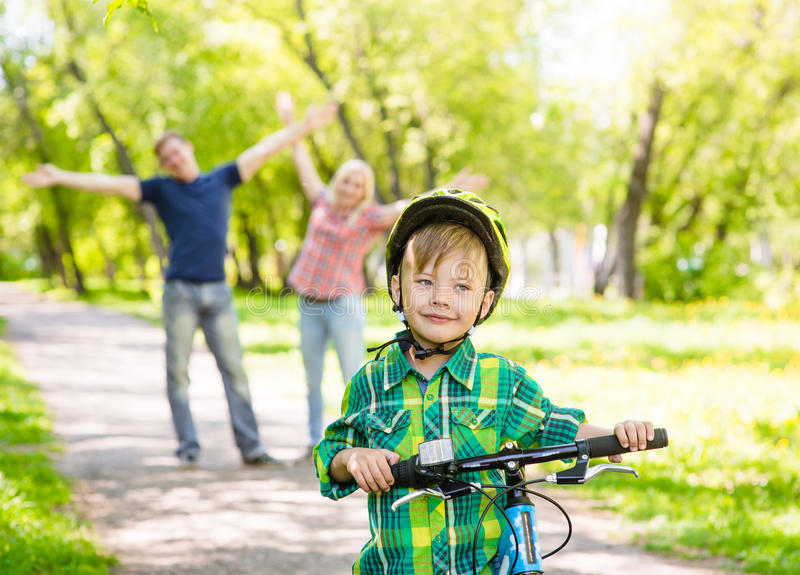 The child learns to ride a bike with his parents in the park.  royalty free stock photography
