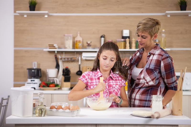 Child leping mother prepare delicious food for both of them stock images