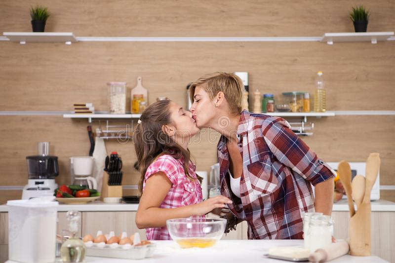 Child leping mother prepare delicious food for both of them royalty free stock photography