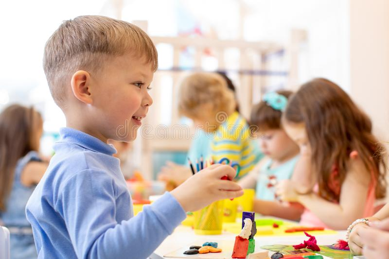 Child on lesson in classroom. Preschool kids group hands crafting in kindergarten stock photos