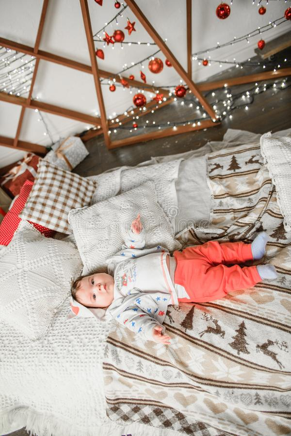 The child lies in the New Year`s atmosphere. Christmas decorations for the baby. in anticipation of the festive New Year`s mirac stock photos
