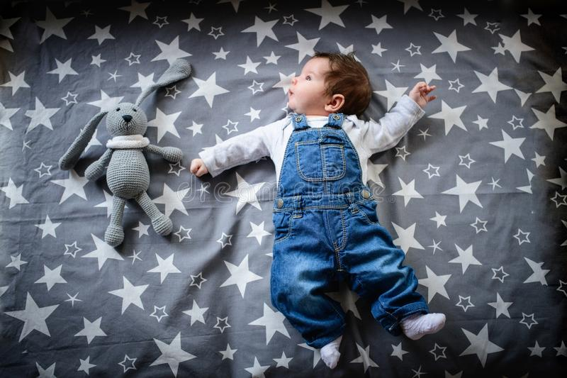 The child lies on a star blanket. Cute newborn baby girl lying in bed. Owl child sleeping on a blue blanket with stars. in stock photo