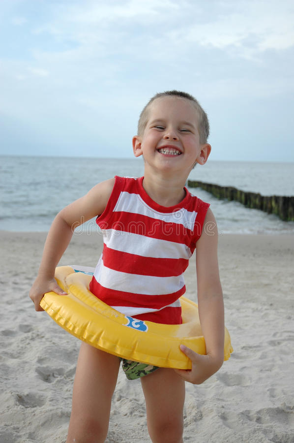 Child with lifebelt. Young child is standing on the beach with lifebelt royalty free stock photos