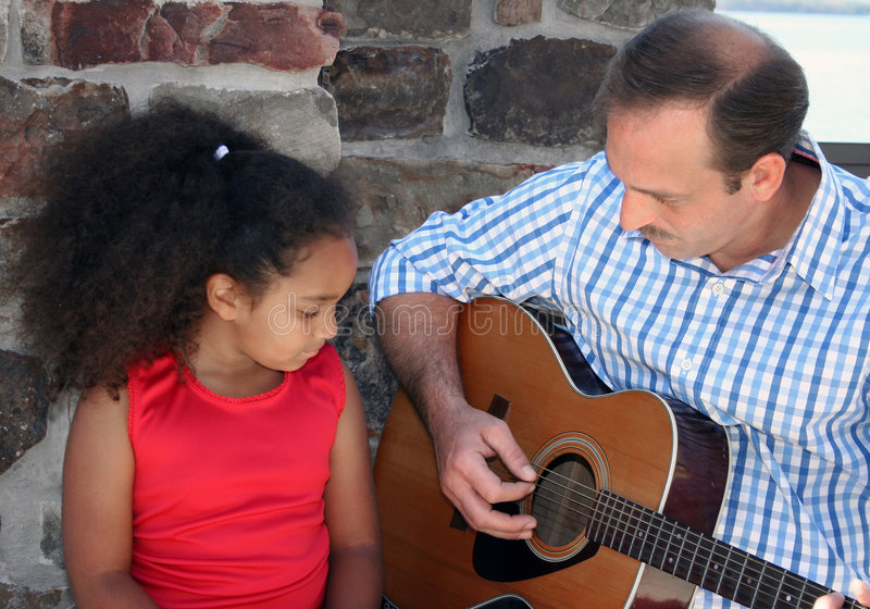 Child listening to guitar. Middle aged man playing guitar for cute multiracial child stock images