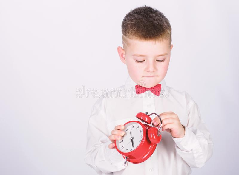 Child little boy hold red clock. It is time. Morning routine. Schoolboy with alarm clock. Kid adorable boy white shirt. Red bow tie. Develop self discipline stock photography