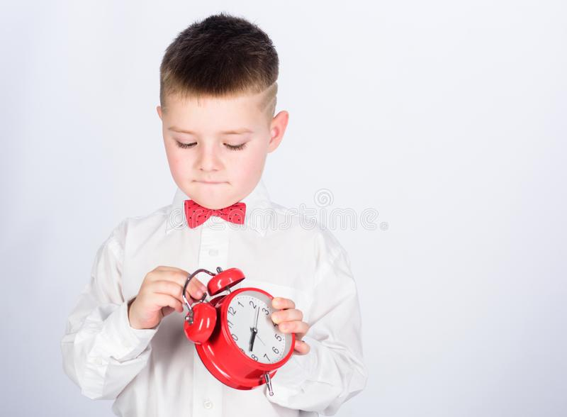 Child little boy hold red clock. It is time. Morning routine. Schoolboy with alarm clock. Kid adorable boy white shirt. Red bow tie. Develop self discipline royalty free stock photo