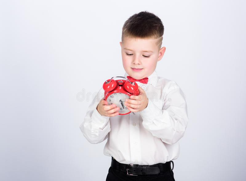 Child little boy hold red clock. It is time. Schedule and timing. Morning routine. Schoolboy with alarm clock. Kid. Adorable boy white shirt red bow tie stock photo