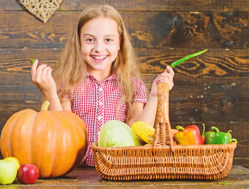 Child little girl enjoy farm life. Organic gardening. Kid farmer with harvest wooden background. Grow your own organic. Food. Girl kid at farm market with royalty free stock images