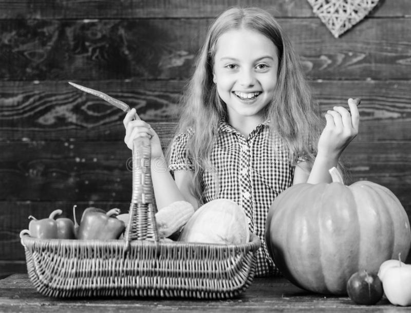 Child little girl enjoy farm life. Organic gardening. Kid farmer with harvest wooden background. Grow your own organic. Food. Girl kid at farm market with stock image