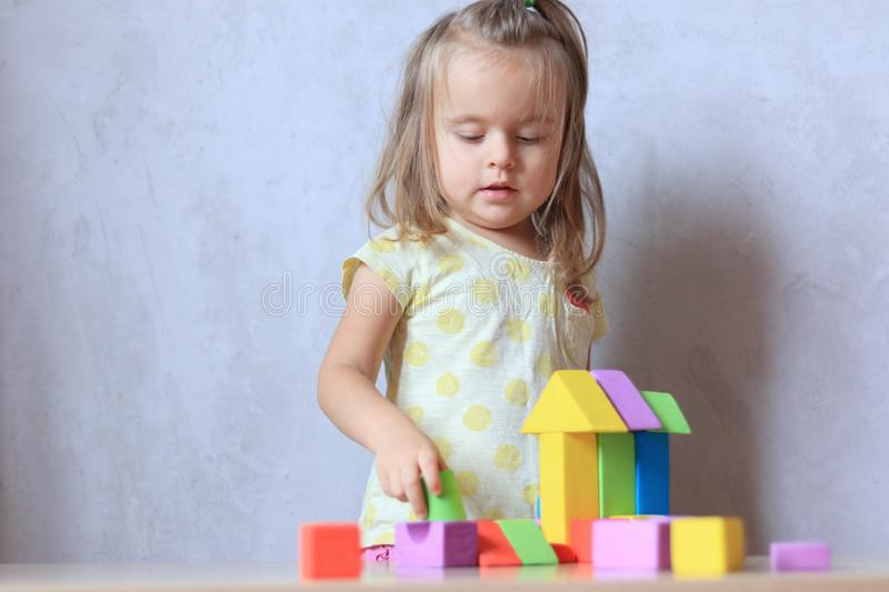 Child little girl playing constructor toys at home stock images