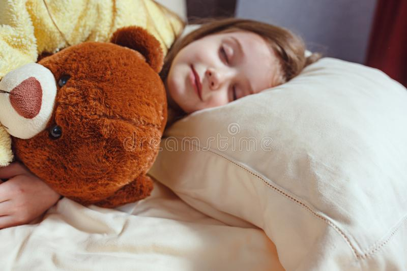 Child little girl sleeps in the bed with a toy teddy bear stock images
