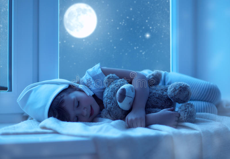 Child little girl sleeping at window dreaming and admiring the s royalty free stock photos