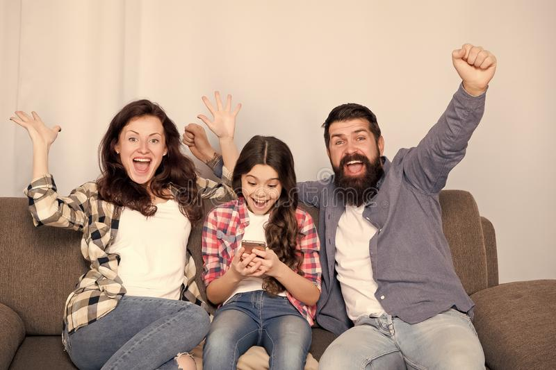 Child little girl use smartphone with parents. Friendly family having fun together. Mom dad and busy daughter relaxing. On couch. Family leisure. Parental stock photos