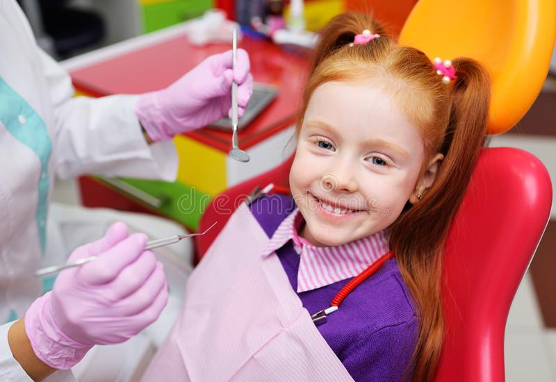 The child is a little red-haired girl smiling sitting in a dental chair. Pediatric dentistry, baby teeth stock image