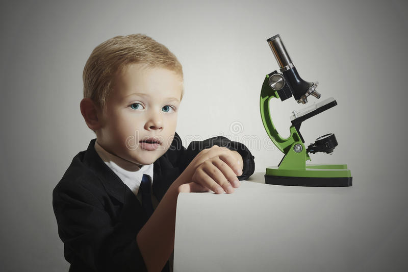 Child.little scientist.little boy in tie.Schoolboy working with a microscope.Education stock images