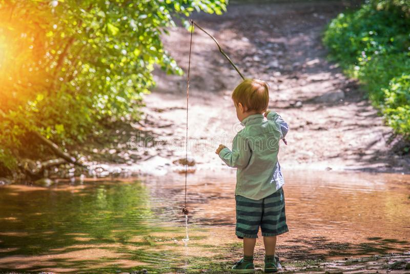 Cute little boy kid fishing in forest stock photography