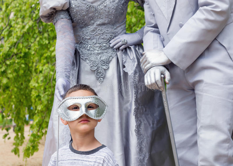 Child with living statues. Child boy posing with two living statues in a park royalty free stock photos