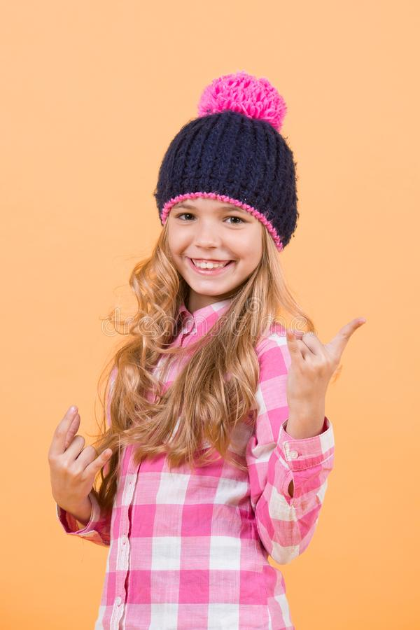 Child with long blond hair smile with horn hands. Girl in hat, plaid shirt on orange background. Beauty, look, hairstyle. Fashion, style, trend. Happy stock photo