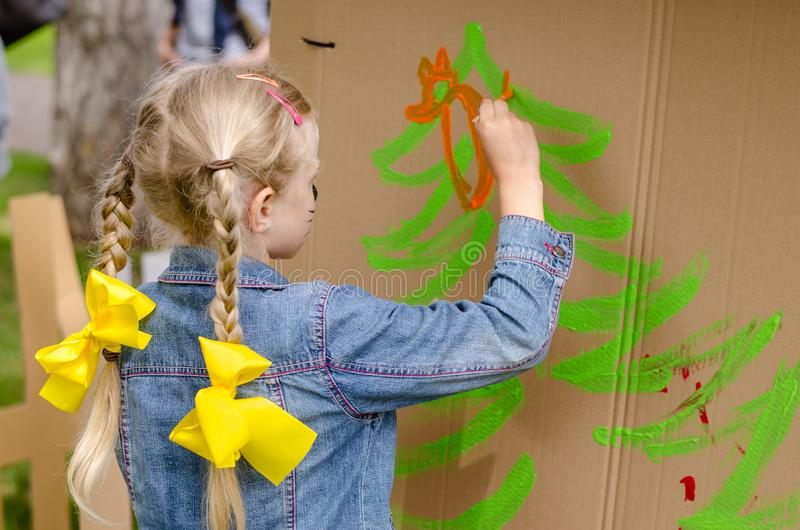 Child with long blond hair in tail and yellow ribbon painting with colors stock image