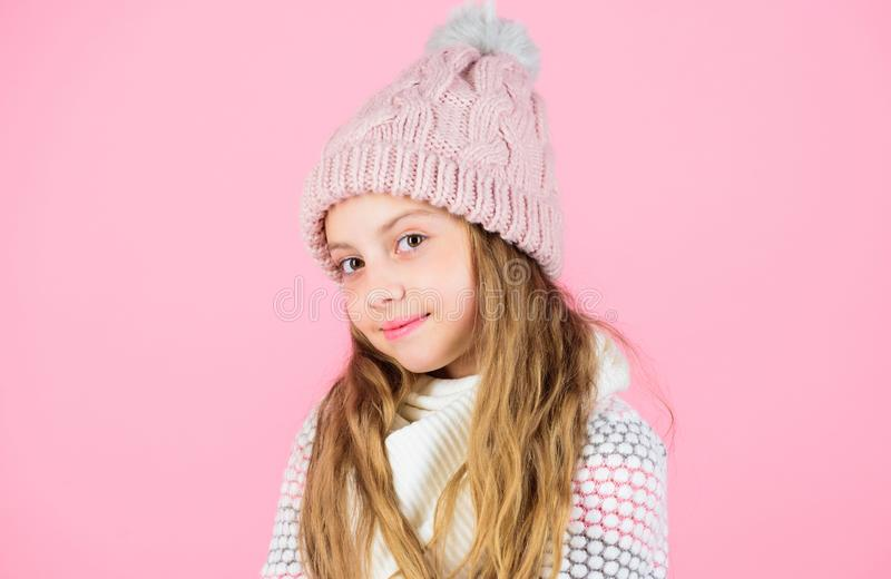 Child long hair warm soft woolen hat enjoy softness. Kid girl wear knitted soft hat pink background. Keep knitwear soft stock photo