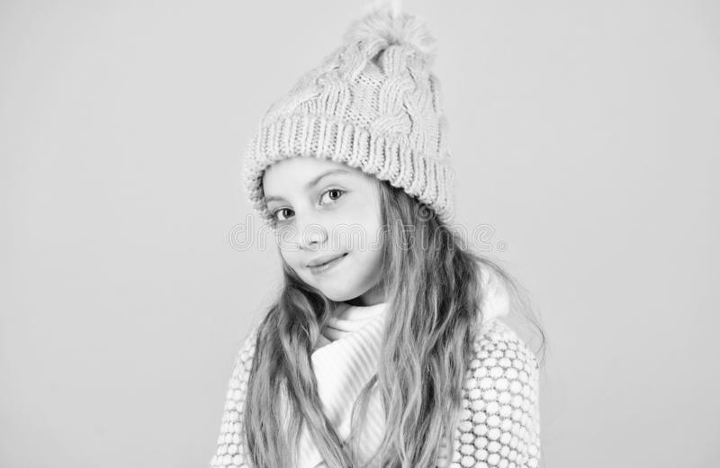 Child long hair warm soft woolen hat enjoy softness. Kid girl wear knitted soft hat pink background. Keep knitwear soft royalty free stock photography