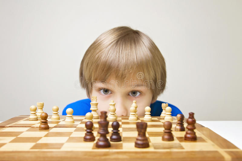 Child looking at chess board. stock photo