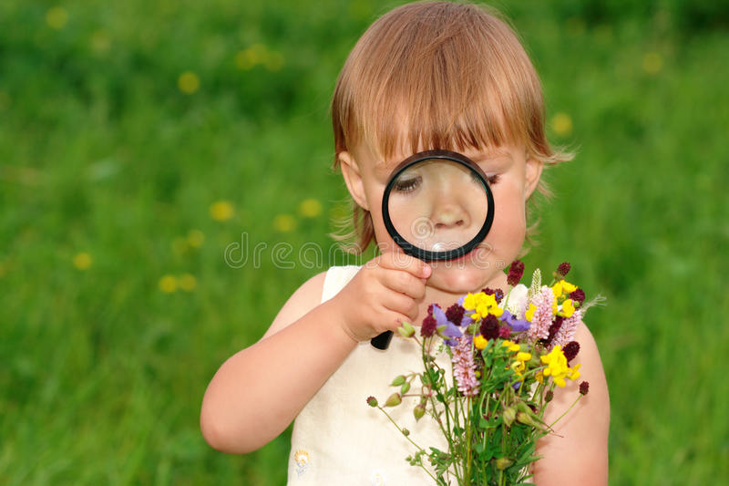 Child looking at flowers through magnifying glass royalty free stock photos