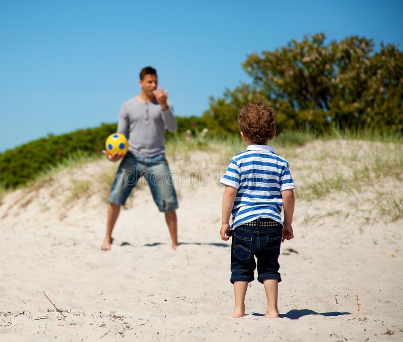 Child Looking at His Dad Teaching Him Soccer. Child looking at his dad teaching him how to play soccer outdoors royalty free stock images