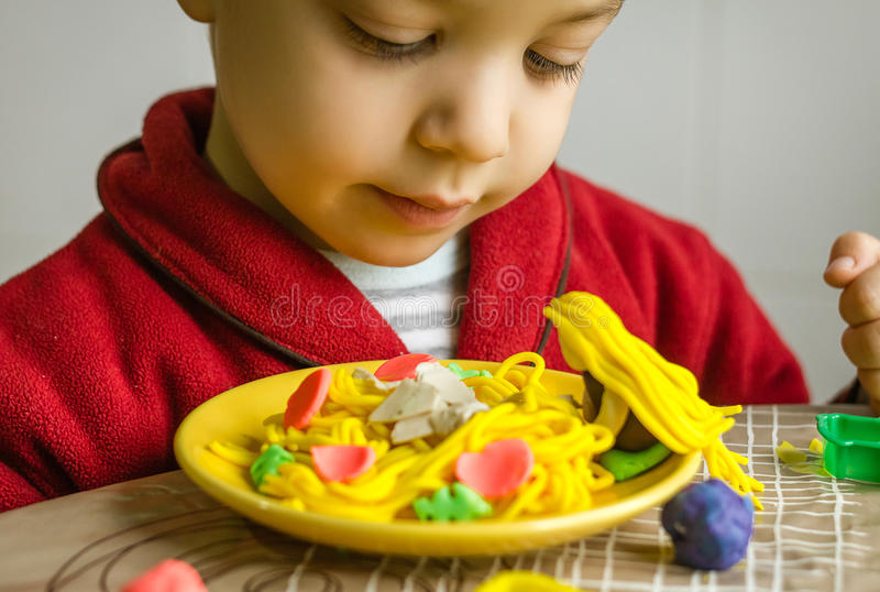 Child looking his spaghetti dish, made with plasticine royalty free stock image
