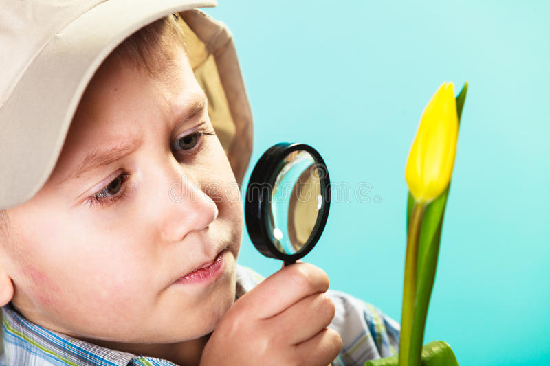 Child looking through a magnifying glass royalty free stock photography