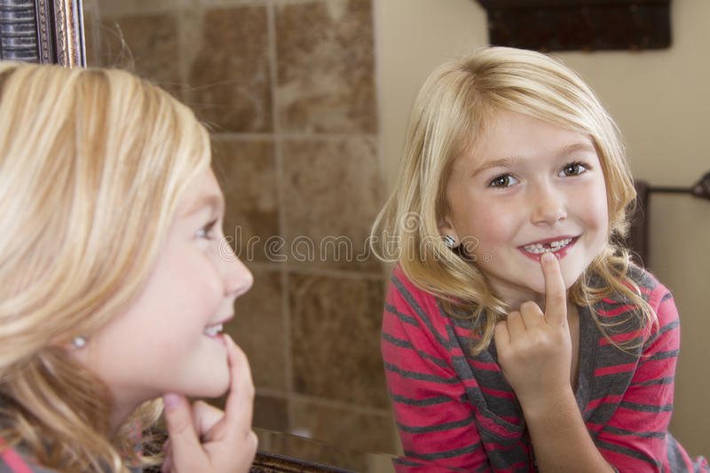 Child looking in mirror at missing front tooth. Child looking in mirror and pointing at missing front tooth stock photography